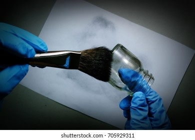 crime scene invest by use powder and brush to develop latent fingerprint