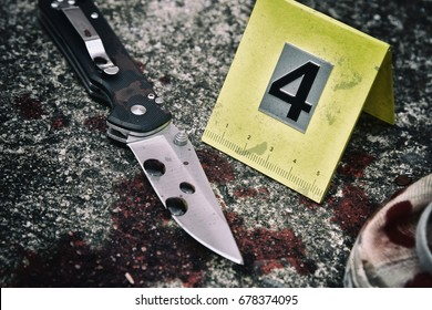 Crime scene investigation, Bloody knife and victim's shoes with criminal markers on ground, Homicide evidence. (Selective Focus)