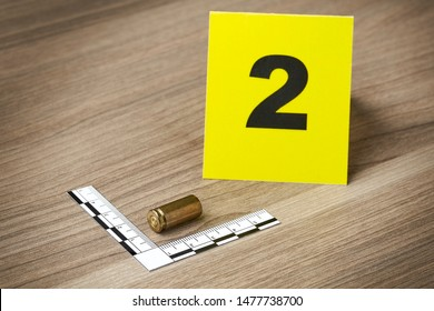 Crime Scene Investigation - bullet casing as a piece of evidence placed with forensic ruler and yellow marker for documentation