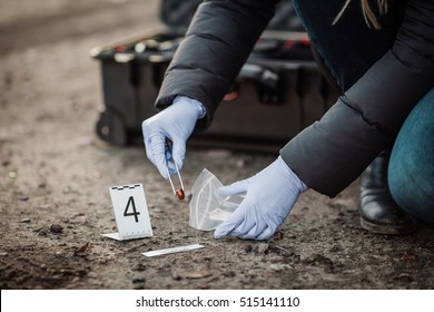 Crime scene investigation - collecting bullet of pistol on the ground