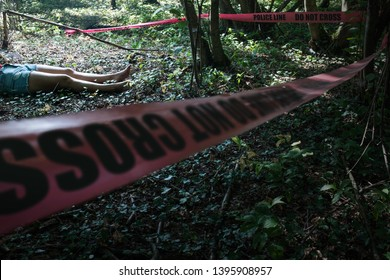 """Crime scene investigation, female corpse lying in the forest, surrounded with red cordon police tape, """"POLICE LINE DO NOT CROSS"""" sign, homicide or suicide concept"""