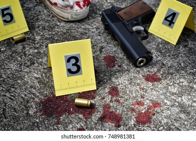 Crime scene investigation, Pistol and bullet shell with blood stain against the crime marker on the ground.