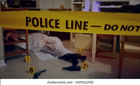 A crime scene in a kitchen with murder victim on the floor, covered with a sheet. Gun, bullet shells, police tape and lights.
