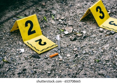 Crime scene marker next to tossed syringe on the ground
