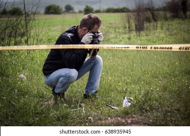 The crime scene, murder, investigation, bloody knife on the grass, an investigation is underway, expert witness with a camera image evidence for murder