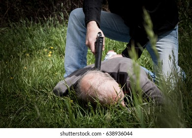 The crime scene, murder, investigation, police caught the killer and detained, killer lying on the grass with his hands behind his back, his cop with a gun at his head