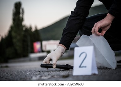 The crime scene, murder, investigation, police find rejected the gun used by the murderer, taken as evidence of the murder, an expert with rubber gloves and takes go in the bag as evidence