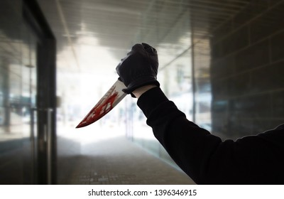 crime scene, murder and killing concept - close up of criminal or murderer hand in leather glove with blood on knife over dark tunnel background (staged photo)