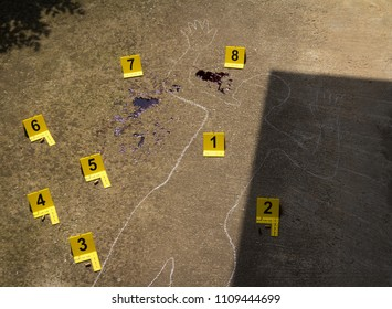 Crime scene. Shape of body on concrete texture. Traces tagged with numbers