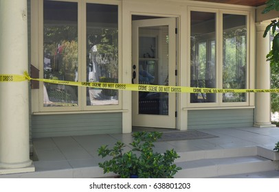 CRIME SCENE AT SOMEONE'S HOME.  CSI Tape Stretched Across The Front Door.  Property release.