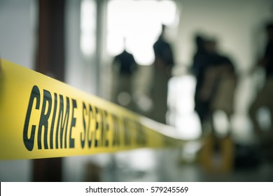 crime scene tape with blurred forensic law enforcement background in cinematic tone and copy space