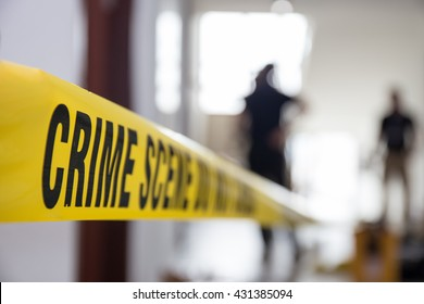 crime scene tape in building with blurred forensic team background
