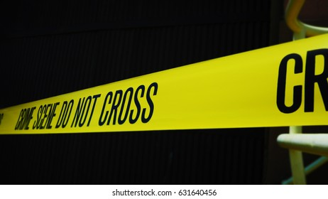 CRIME SCENE TAPE IN CLOSE UP, WITH BLACK BACKGROUND.