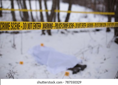 Crime scene tape and dead body blurred in background.