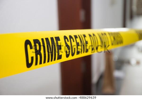 crime scene tape in front of room door with blurred background