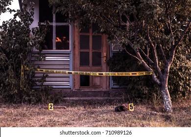 Crime scene tape near the house, police tape Do Not Cross outdoors