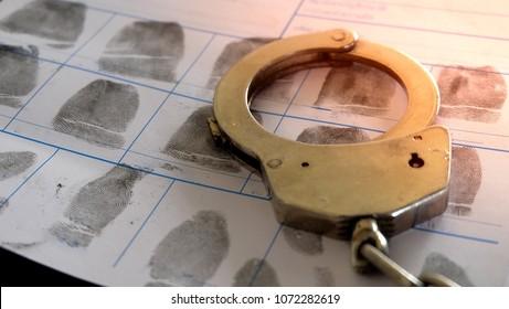 Crime and violence concept.Police Handcuffs on  fingerprints crime page file