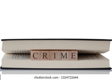 Crime written on wooden blocks inside a book isolated on a white background with reflection