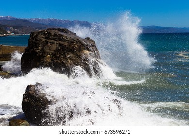 Crimea. Alushta. Sea. The wave beats against the rock and spreads out with splashes. Bright blue sky and mountains.