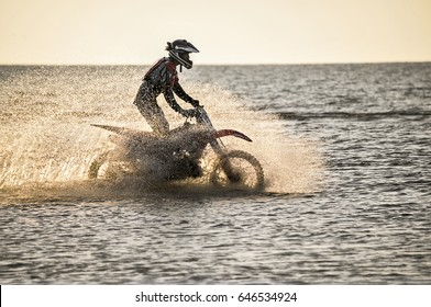 CRIMEA .BLACK SEA - May 07 ,2017 : A rider on a cross-country motorcycle rides by the sea and raises a spray of water