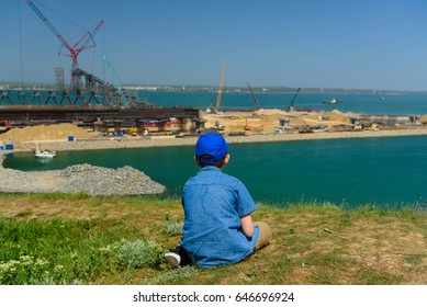 Crimea, Kerch - May 04, 2017: A boy is watching The Kerch Strait Bridge construction