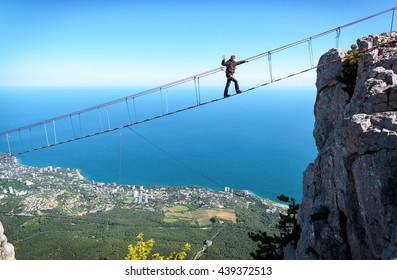CRIMEA - MAY 19, 2016: Tourist walking on a rope bridge on Mount Ai-Petri. Amazing view of the high rope bridge with traveler above abyss against the Black Sea coast. Scenery of Crimea in summer.