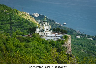 Crimea, Russia -13 May, 2015: Church in Foros built in 1892 on a steep mountain cliff. Green mountainside and blue Black Sea.