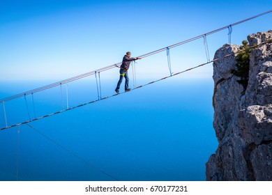 CRIMEA, RUSSIA - MAY 19, 2016: Tourist walks on a rope bridge on the Mount Ai-Petri over the chasm. Ai-Petri is one of the highest peaks in Crimea and tourist attraction. Challenges in the mountains.