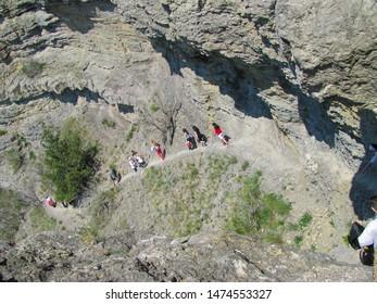 Crimea, tourists on a steep mountain trail, dangerous cliffs and steeps