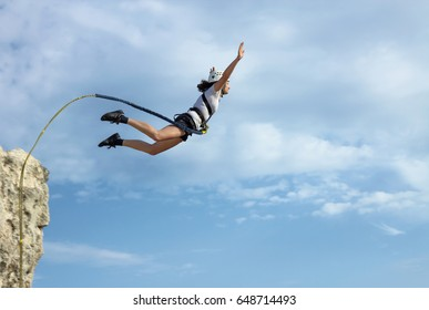 CRIMEA, UKRAINE,  AUGUST 2011 : Young woman jump from the cliff with a rope