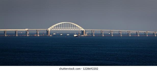 Crimean bridge road across Kerch Strait with leading cargo ships. Sea gate to the sea of Azov