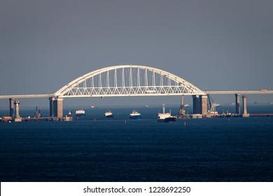 Crimean bridge road across Kerch Strait with leading cargo ships. Sea gate to the  Azov sea
