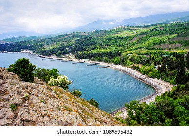 Crimean coast city of Partenit. Embankment of Partenit village top view. Seaside promenade. Beautiful view of small town on the Black Sea coast against the blue sky with clouds. Crimea mountains.