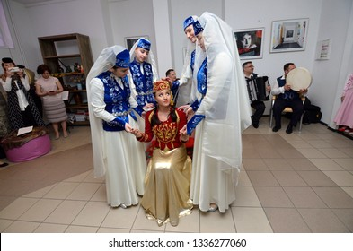 Crimean Tartar traditional wedding ceremony: bridesmaids preparing a bride (center, in a red dress) to meet a groom. Days of Crimean Tartar culture. February 27, 2019. Kiev, Ukraine