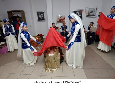 Crimean Tartar traditional wedding ceremony: bridesmaids preparing a bride for meeting a groom by covering her red cloth. Days of Crimean Tartar culture. February 27, 2019. Kiev, Ukraine