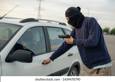 criminal accident, burglar threatening the car driver with a pistol on the parking