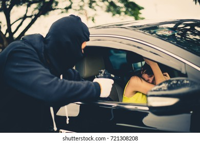 Criminal or Bandit wear black mask use gun point to woman in black car at the parking trying to rob money and hurting her. Woman is threatened with reproached gun in the car, Carjacking