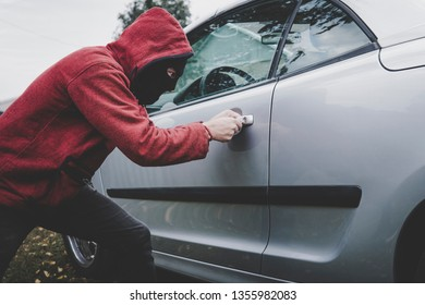 Criminal in black balaclava and hoodie opens somebody's vehicle with skeleton key. Car breaking by unknown male with hidden face. Young man picks automobile lock to get inside. Forcing the car door.