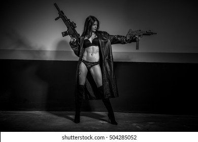 Criminal brunette girl with long leather coat and lingerie with machine gun and pistol posing dangerous in a garage