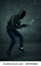 Criminal in dark clothes and balaclava with the laptop