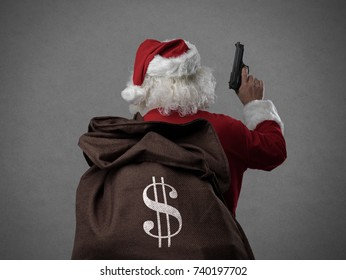 Criminal disguised as Santa Claus holding a gun and carrying a sack full of stolen money, he is robbing houses on Christmas Eve's night