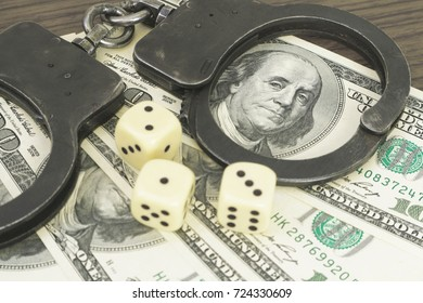Criminal gambling. Handcuffs and dice on dollars. Detention for fraud.