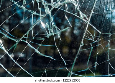 Criminal incident at the bus stop. Shooting a pistol. Hole and cracks in the glass of a city bus stop. Cracked glass texture against the blue sky. Cracked glass with a hole from a bullet. Vandalism