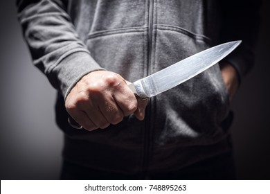 Criminal with knife weapon threatening to stab