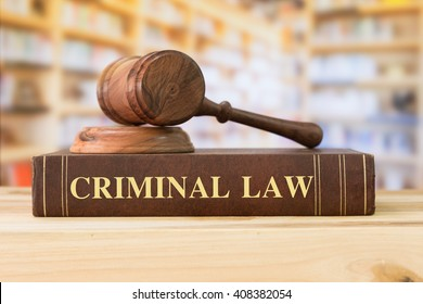 Criminal Law books with a judges gavel on desk in the library. Legal education concept.