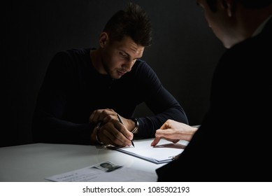 Criminal man with handcuffs signing document in interrogation room after committed a crime