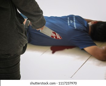Criminal or murderer with knife in blood and dead man body lying on floor at crime scene. murder, kill and people concept.