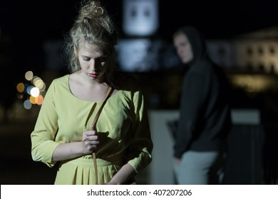 Criminal observing young woman walking alone at night