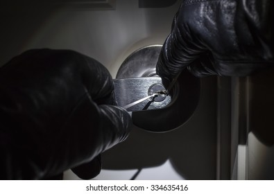 Criminal Picking Lock with Black Leather Gloves at Night