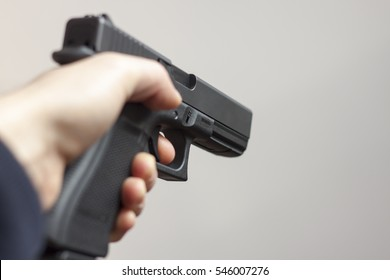 Criminal pointing a gun. Robbery concept with man holding a gun and threatening